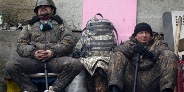 Anti-government protesters rest as they man a barricade in central Kiev, Ukraine, Friday, Feb. 21, 2014.  European officials say Ukrainian protesters have agreed to a deal with Ukraine's president on defusing a deadly political crisis. Earlier Friday President Viktor Yanukovych announced early elections and promised to invite the opposition into the government. (AP Photo/Darko Bandic)