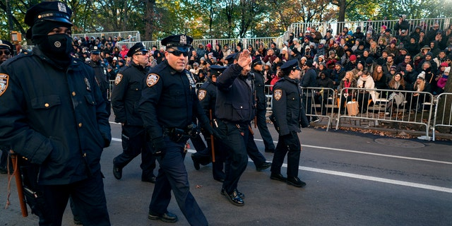 New York Police Department officers are greeted by people before the start of the Macy's Thanksgiving Day Parade in New York, Thursday, Nov. 23, 2017.