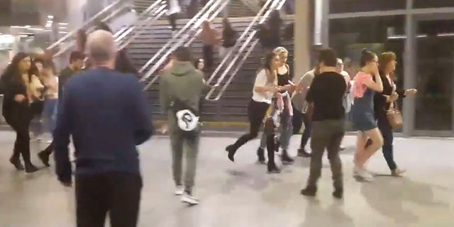 This image shows  people running through Manchester Victoria station after an explosion at Manchester Arena. in Manchester England, Monday May 22, 2017. An apparent suicide bomber set off an improvised explosive device that killed over a dozen people at the end of an Ariana Grande concert on Monday, Manchester police said Tuesday May 23, 2017.  The station is very near the arena. (Zach Bruce/PA via AP)