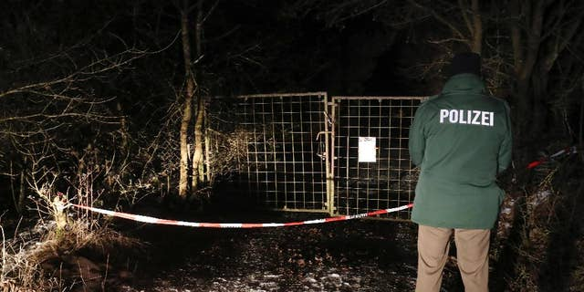 A police officer stands in front of a closed off entrance to a private ground near Arnstein, Germany, Sunday Jan. 29, 2017. Police in Germany say the bodies of six teenagers have been found dead in a garden house near the southern city of Wuerzburg. (Daniel Karmann/dpa via AP)
