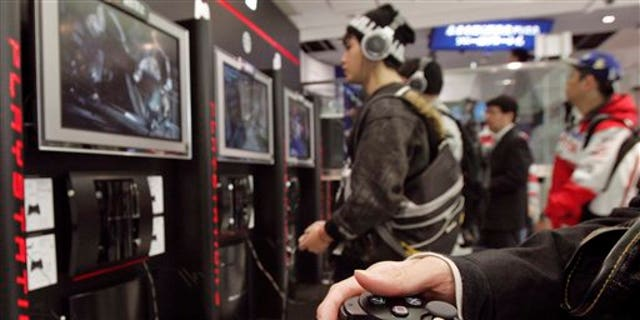 FILE - In this Nov. 9, 2006 file photo, visitors at the Sony Building in downtown Tokyo play Sony's next-generation video game PlayStation 3 as its two-week-long free trial service goes on. Sony Corp. said Tuesday, April 26, 2011 that the credit card data of PlayStation users around the world may have been stolen in a hack that forced it to shut down its PlayStation Network for the past week, disconnecting 77 million user accounts. (AP Photo/Katsumi Kasahara, File)