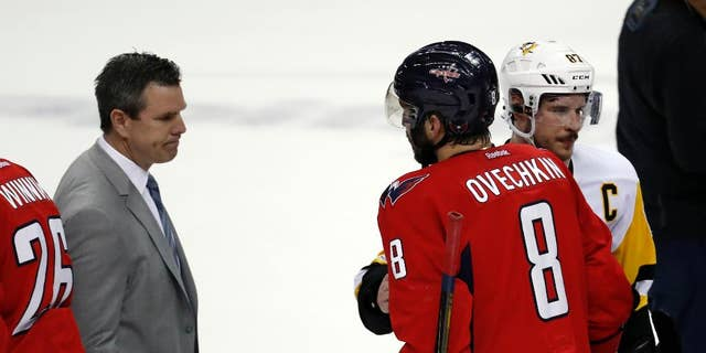 Pittsburgh Penguins coach Mike Sullivan, left, waits to greet Washington Capitals left wing Alex Ovechkin (8), from Russia, who is talking with Penguins center Sidney Crosby (87) after Game 7 in an NHL hockey Stanley Cup Eastern Conference semifinal, Wednesday, May 10, 2017, in Washington. The Penguins won 2-0. (AP Photo/Alex Brandon)