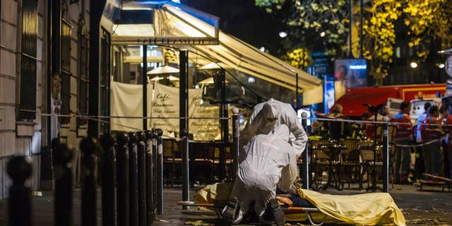 In this Friday, Nov. 13, 2015 file photo of Investigating police officers inspect the lifeless body of a victim of a shooting attack outside the Bataclan concert hall in Paris, France. AP Photo/Kamil Zihnioglu