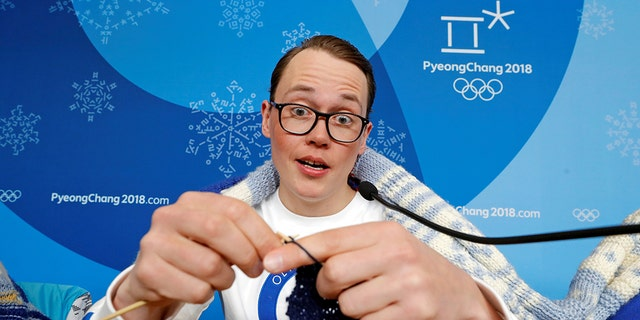 Antti Koskinen, snowboard head coach, shows how he knits, during a news conference in Pyeongchang, South Korea, February 14, 2018.