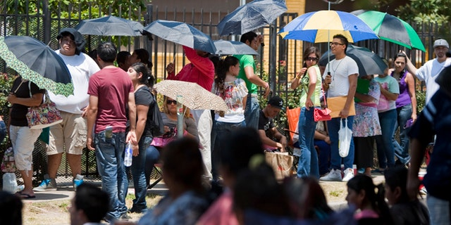 Illegal immigrants wait in line to get passports outside the Mexican Consulate in Houston in August, after the Department of Homeland Security began accepting applications to allow them to avoid deportation. (AP)