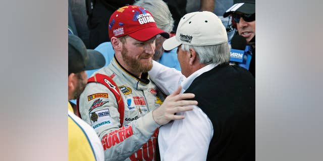 Dale Earnhardt Jr. celebrates winning the NASCAR Sprint Cup Series auto race with team owner Rick Hendrick, front right, in Victory Lane at Martinsville Speedway in Martinsville, Va., Sunday, Oct. 26, 2014. (AP Photo/Steve Helber)