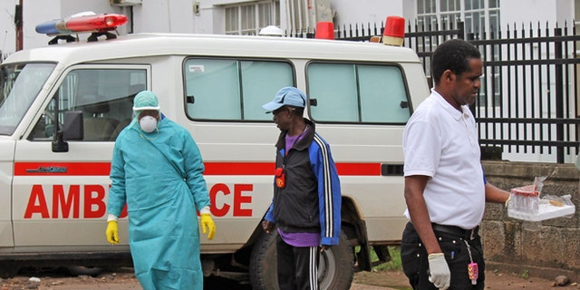 In this photo taken on Monday, Aug. 4, 2014,  health workers outside Connaught Hospital, after the arrival of patient with symptoms of the Ebola virus in the city of  Freetown, Sierra Leone. The global Ebola outbreak touched American shores more definitively Monday, as Atlanta awaited the arrival of its second Ebola patient by morning, and a New York hospital announced it had isolated a man with possible symptoms who walked into its emergency room.(AP Photo/ Youssouf Bah)