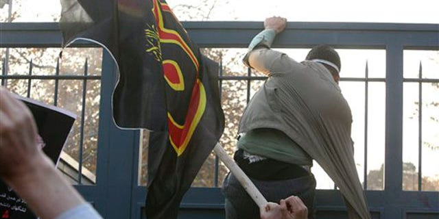 November 29, 2011: An Iranian protester tries to enter the British Embassy, as he is prevented by police.