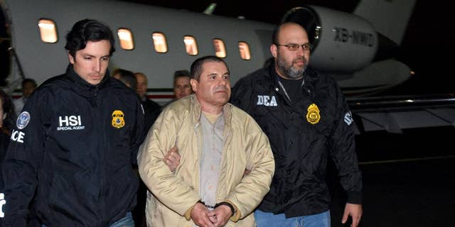 "In this photo provided U.S. law enforcement, authorities escort Joaquin ""El Chapo"" Guzman, center, from a plane to a waiting caravan of SUVs at Long Island MacArthur Airport on Thursday, Jan. 19, 2017, in Ronkonkoma, N.Y."