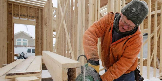 In this Wednesday, Feb. 18, 2015 photo, carpenter Joe Tominc cuts wood for a post on a home under construction in Pepper Pike, Ohio. The Commerce Department reports on U.S. construction spending in January on Monday, March 2, 2015. (AP Photo/Tony Dejak)