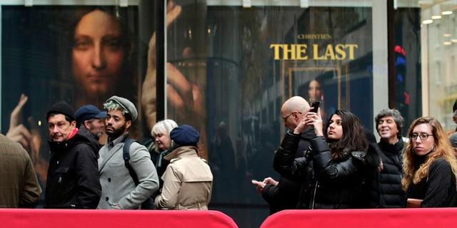 "Visitors to Christie's wait outside in a line to view Leonardo da Vinci's ""Salvator Mundi"", Tuesday, Nov. 14, 2017, in New York."