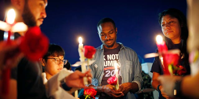 Maurice Forbes, center, holds a candle with others during a vigil at The Center, a community center for the LGBT community, Sunday, June 12, 2016, in Las Vegas. The vigil was for the victims of the Pulse nightclub shooting in Orlando. (AP Photo/John Locher)