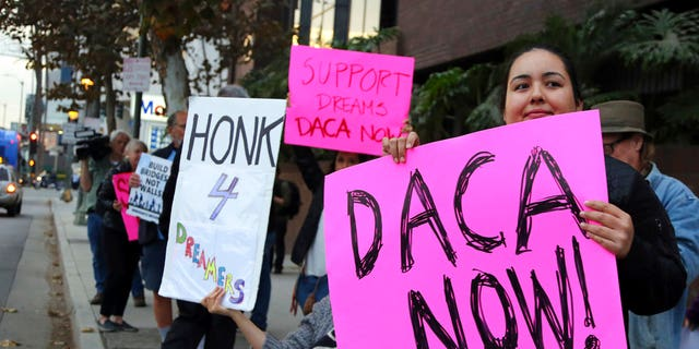 Demonstrators urging the Democratic Party to protect the Deferred Action for Childhood Arrivals Act (DACA) rally outside the office of California Democratic Sen. Dianne Feinstein in Los Angeles Wednesday, Jan. 3, 2018. California has the largest number of people who are affected by the law, also known as the Dream Act.(AP Photo/Reed Saxon)