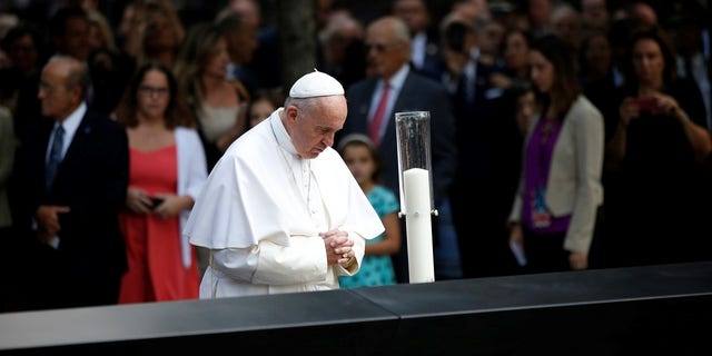 Pope Francis is seen praying at the 9/11 memorial.