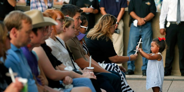 Family and friends of fallen police officers take part in a candlelight vigil at City Hall on Monday, July 11, 2016, in Dallas. Five police officers were killed and several injured during a shooting in downtown Dallas last Thursday night. (AP Photo/Tony Gutierrez)