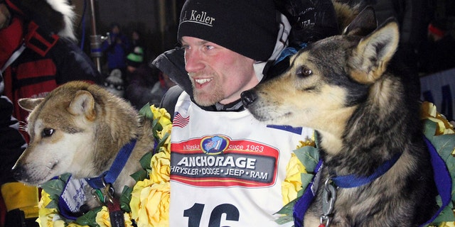 In this March 15, 2016, file photo, Dallas Seavey poses with his lead dogs Reef, left, and Tide after finishing the Iditarod Trail Sled Dog Race in Nome, Alaska.