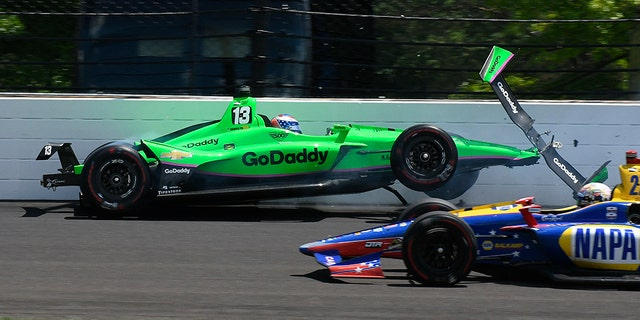 Alexander Rossi drives by Danica Patrick as she hits the wall in the second turn.
