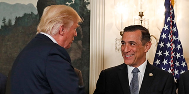President Donald Trump, left, greets Rep. Darrell Issa, R-Calif., in the Diplomatic Reception Room of the White House in Washington, Monday, Aug. 14, 2017, before an event to sign a memorandum calling for a trade investigation of China. (AP Photo/Alex Brandon)