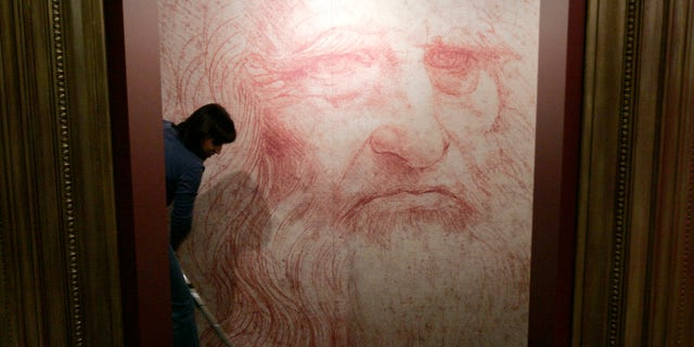 "File photo - A cleaner vacuums in front of a Leonardo da Vinci self-portrait drawn around 1515 or 1516, during the inauguration of the exhibition ""Leonardo da Vinci, the European Genius"" in Brussels, August 17, 2007."