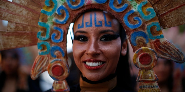 A woman in costume smiles as she waits for the start of a Day of the Dead celebration in Mexico City.