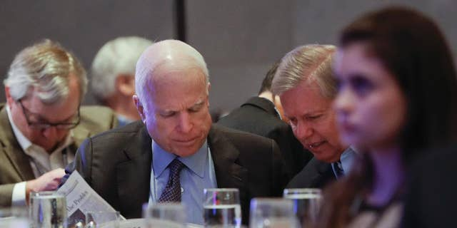 In this Jan. 26, 2017, photo, Sen. John McCain, R-Ariz., left, and Sen. Lindsey Graham, R-S.C., right, read the Wall Street Journal newspaper as they wait for President Donald Trump to speak at the House and Senate GOP lawmakers at the annual policy retreat in Philadelphia. McCain has emerged as Trump's top Republican nemesis on Capitol Hill. Since Trump's inauguration, McCain has broken with the president on his immigration order, warned him against any rapprochement with Moscow and lectured him on the illegality of torture. He supplied only a tepid endorsement of Rex Tillerson, Trump's secretary of state nominee. (AP Photo/Pablo Martinez Monsivais)