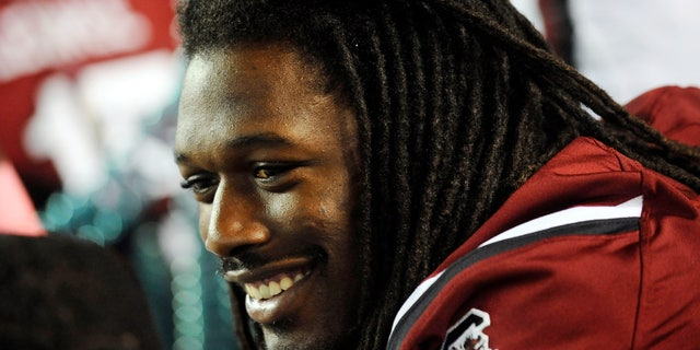 FILE - In this Saturday, Oct. 5, 2013, file photo, South Carolina defensive end Jadeveon Clowney smiles as he sits on the bench during the first half of an NCAA college football game against Kentucky in Columbia, S.C. South Carolina coach Steve Spurrier has said Clowney's availability for Arkansas is up in the air after the All-American defensive end decided not to play in last week's game because of what has been diagnosed as a strained muscle. (AP Photo/Rainier Ehrhardt, File)