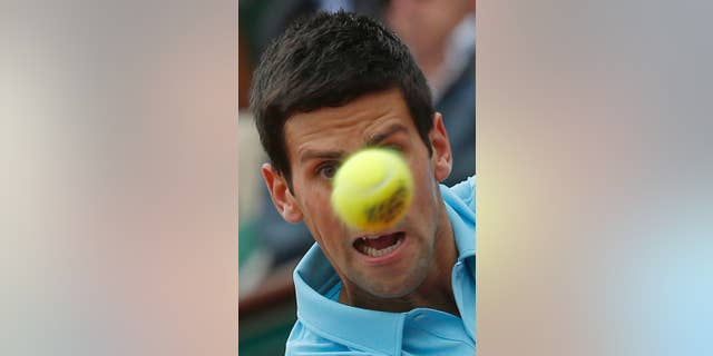 Serbia's Novak Djokovic eyes the ball as he returns during the first round match of the French Open tennis tournament against Portugal's Joao Sousa at the Roland Garros stadium, in Paris, France, Monday, May 26, 2014. (AP Photo/Michel Euler)