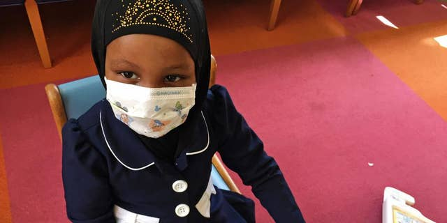 In this Tuesday, May 2, 2017 photo, Amira Hassan, of Burnsville, Minn., plays in the waiting room at the specialty clinic at Children's Minnesota in Minneapolis. Hassan went to the hospital's clinic for a routine wellness check, but had to wear a mask to protect her from measles after an outbreak has sickened more than 30 children in Minnesota. The masks are just one precaution that hospitals are taking to try to control the spread of the disease, which is predominantly affecting Minnesota's Somali community. (AP Photo/Amy Forliti)