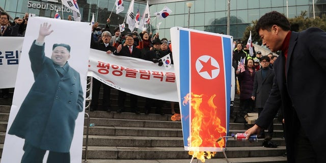 Protesters burn the North Korean flag and photos of Kim Jong Un ahead of the Olympics.