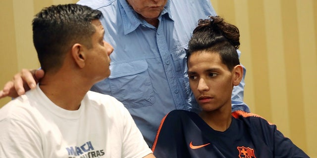 Anthony Borges sits with his father after the lawyer read a statement regarding the attack.