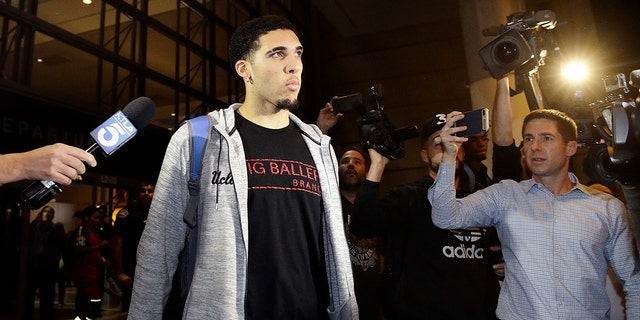 UCLA basketball player LiAngelo Ball is surrounded by reporters and photographers as he leaves Los Angeles International Airport on Tuesday, Nov. 14, 2017, in Los Angeles.