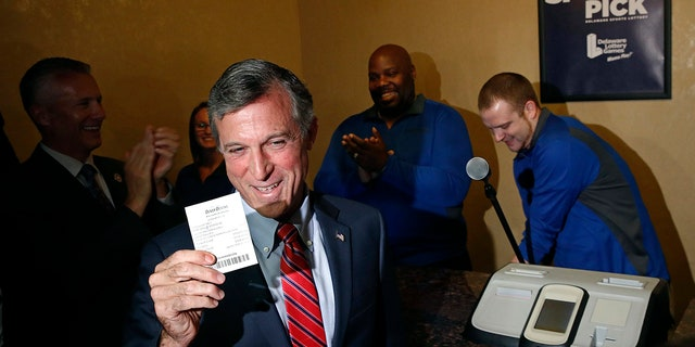 Delaware Gov. John Carney displays a receipt for a bet he placed on a baseball game between the Chicago Cubs and the Philadelphia Phillies inside the Race and Sports Book at Dover Downs Hotel and Casino.