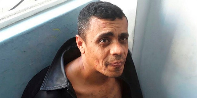 In this photo released by the Military Police, Adelio Bispo de Oliveira, suspected of stabbing Bolsonaro sits after being detained in Juiz de Fora, Brazil on Thursday.