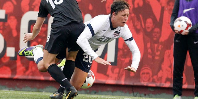 US Women's National Team's Abby Wambach (20) is tripped by New Zealand Women's National Team's Rebekah Stott (15) in the second half of an international friendly soccer match on Sunday, Oct. 27, 2013, in San Francisco. US won 4-1. (AP Photo/Tony Avelar)