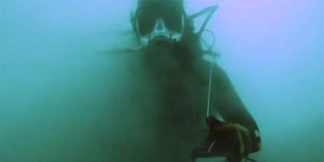 A diver, outfitted with special equipment designed to brave the salty conditions, is partially obscured by the murk of the Dead Sea.