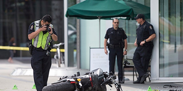"""A police officer photographs a motorcycle after a female stunt driver working on the movie """"Deadpool 2"""" died after a crash on set, in Vancouver, B.C., on Monday Aug. 14, 2017. Vancouver police say the driver was on a motorcycle when the crash occurred on the movie set on Monday morning. (Darryl Dyck/The Canadian Press via AP)"""