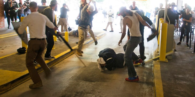 Deandre Harris, bottom, is assaulted in a parking garage beside the Charlottesville Police Station after a white nationalist rally in Charlottesville, Va.