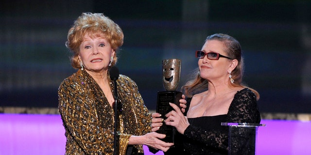 """FILE- In this Jan. 25, 2015, file photo, Carrie Fisher, right, presents her mother Debbie Reynolds with the Screen Actors Guild life achievement award at the 21st annual Screen Actors Guild Awards at the Shrine Auditorium in Los Angeles. """"La La Land"""" star Ryan Gosling thanked Reynolds at the Palm Springs Film Festival on Monday, Jan. 2, 2017, for serving as an inspiration to the cast and crew of the film. (Photo by Vince Bucci/Invision/AP, File)"""