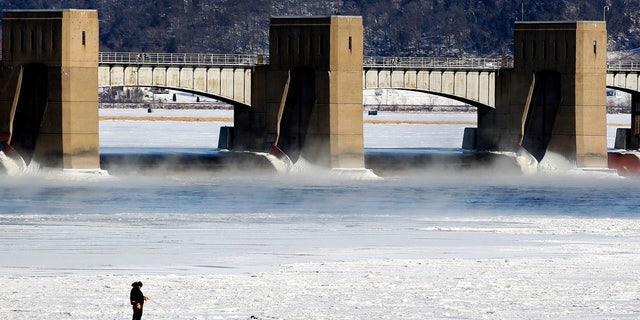 A person fishes near Lock and Dam No. 11 in Dubuque, Ia. The area is seeing bitterly cold temperatures.
