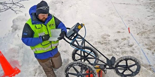 Seth A. Van Dam, a geophysical archaeologist takes notes while investigating potential Native American artifacts that could affect the creation of a new sewer district in Upstate New York