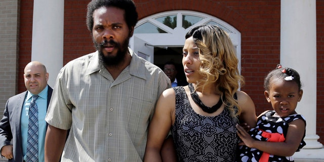 """March 5, 2014: Cornealious """"Mike"""" Anderson walks out of the Mississippi County Courthouse along with his wife, LaQonna Anderson, daughter Nevaeh, 3, and attorney Patrick Megaro, far left, after being released from custody in Charleston, Mo."""