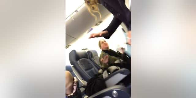 """The woman was ultimately removed from the plane at the flight attendant's request. """"You just screamed at a woman and her baby,"""" the flight attendant told her."""