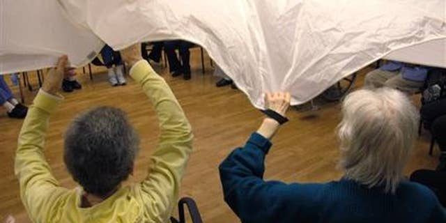 """In this Sept. 20, 2012 photo, dementia patients sitting in a circle formation do an exercise called """"the parachute"""" at the Hebrew Home at Riverdale in the Bronx borough of New York. (AP Photo/Jim Fitzgerald)"""