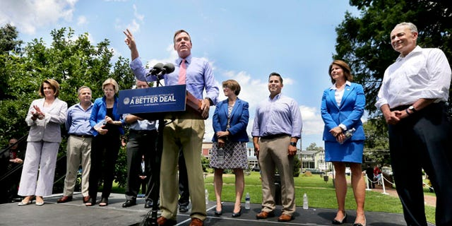 Virginia Sen. Mark Warner speaks about the Democratic Party's economic plan at Rose Hill Park, Monday, July 24, 2017 in Berryville, Va. Warner is flanked by House Democratic leader Nancy Pelosi, from left, Rhode Island Rep. David Cicilline, Massachusetts Sen. Elizabeth Warren, Maryland Sen. Chis Van Hollen, Minnisota Sen. Amy Klobuchar, New Mixico. Rep. Ben Ray Lujan, Illinois Rep. Cheri Bustos and Sen. Democratic leader Chuck Schumer. (Scott Mason/The Winchester Star via AP)