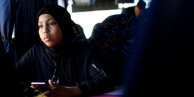 """Ibtisam Ashur, a resident of Mjolnerparken which is a housing estate that features on the Danish government's """"Ghetto List"""", rides a bus during an excursion to the seaside with """"Sjakket"""", a youth group that provides activities and support for children that live in socially vulnerable areas of Copenhagen's north-west area in Denmark, May 9, 2018."""