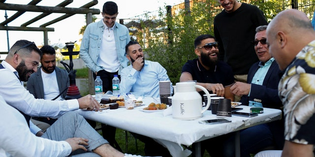 "Guests from places within Denmark and Northern Europe sit together at the engagement party of a resident in Mjolnerparken, a housing estate that features on the Danish government's ""Ghetto List"", in Copenhagen, Denmark, May 6, 2018."