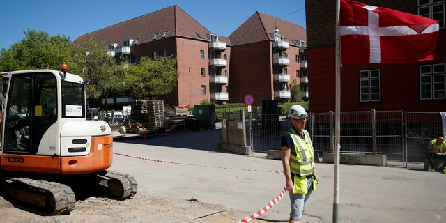 """A worker stands beside a Danish flag on a construction site of new housing being built next to Mjolnerparken, a housing estate that features on the Danish government's """"Ghetto List"""", in Copenhagen, Denmark, May 8, 2018."""