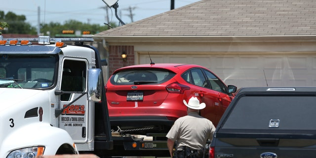 A vehicle is towed as Denton County Sheriff's officers investigate the crime scene.