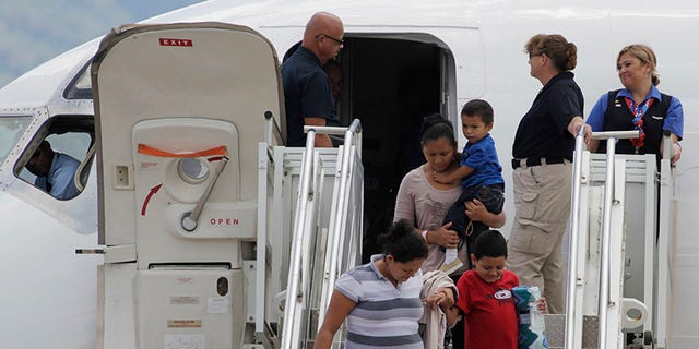 Women hold their children while disembarking from a plane at the Soto Cano military base in Comayagua August 11, 2014. The plane carrying 11 women and 14 children landed at the base after they had been deported from the U.S. While the White House says the number of Central American child migrants crossing the U.S. border has fallen sharply, the big unanswered question remains why. The U.S. government has pointed to the seasonal weather. However, Reuters reporting in southern Mexico and Central America shows it is due to a combination of factors, including tighter border policing, horror tales told by deportees who grappled with drug gangs, an advertising blitz touting the dangers of making the journey and the high-profile arrests of several human smugglers, or coyotes. Picture taken August 11. To match Insight USA-IMMIGRATION/DECLINE                   REUTERS/Jorge Cabrera (HONDURAS - Tags: SOCIETY IMMIGRATION POLITICS MILITARY TRANSPORT) - RTR422BX