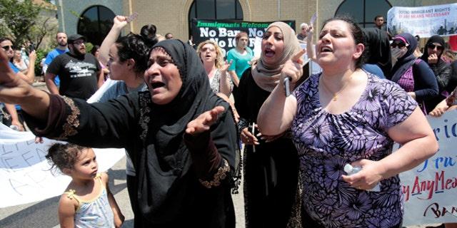 A group of women react as they talk about family members seized on Sunday by Immigration and Customs Enforcement agents during a recent rally in Southfield, Michigan.